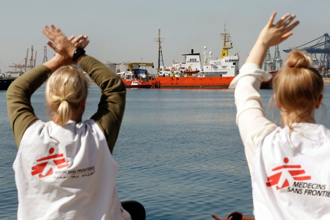 Two women wearing shirts of the relief organization Medecins Sans Frontieres waved to the Aquarius (background), which carried migrants as it entered the port of Valencia, Spain, last month. The French NGO ship carrying some 630 migrants had been headed to Italy before Spain. Italy's stance against migration recently reached a new level with government officials refusing a private Italian ship from entering its ports with rescued migrants. File Photo by EPA-EFE/Juan Carlos Cardenas