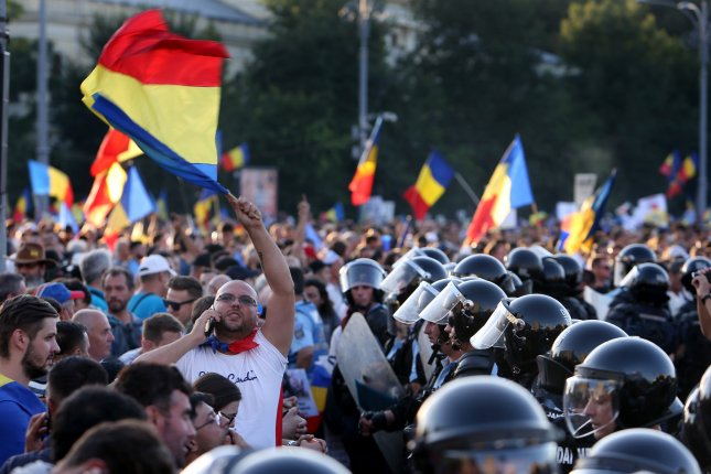 A Romanian protester (center L) waves the national flag during a protest against the government Friday in Bucharest, Romania. Photo by Bogdan Cristel/EPA-EFE