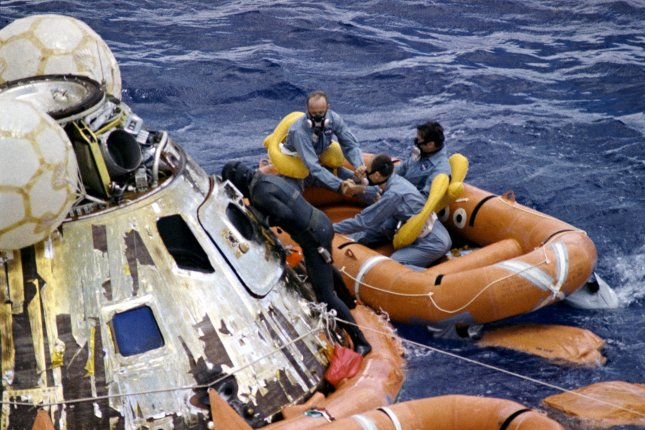 A U.S. Navy underwater demolition team swimmer assists the Apollo 12 crew during recovery operations in the Pacific Ocean on November 24, 1969. File Photo courtesy of NASA