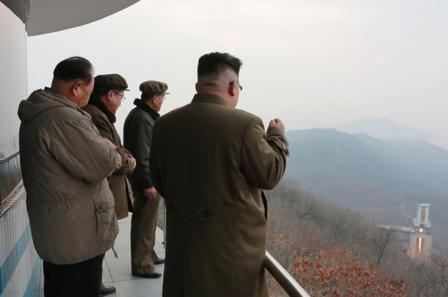 North Korean leader Kim Jong Un (R) watches the test of a high-thrust rocket engine, according to KCNA in March. North Korea cyberattacks are being launched to procure funds for the state's weapons program, according to a recent report. Photo by KCNA/EPA