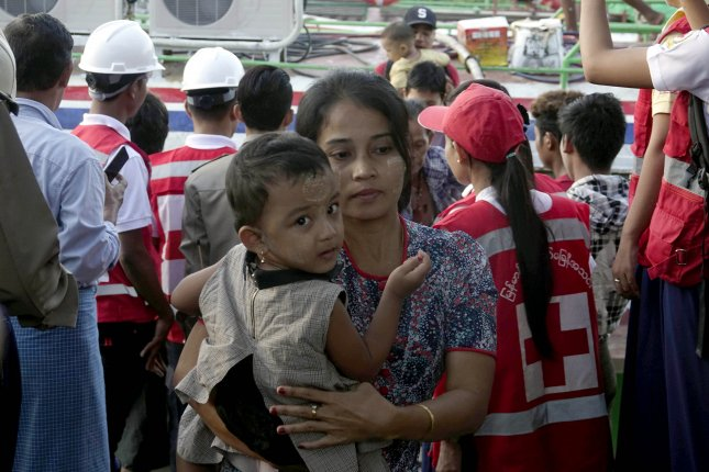 A displaced Rakhine woman with her daughter from Maungdaw township arrive at the Sittwe port in western Myanmar on Monday. Photo by EPA