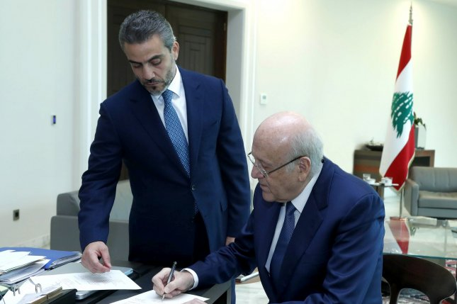 Lebanon's Prime Minister Najib Mikati (R) signs the new government decree at the Presidential Palace in Beirut on Friday. Photo courtesy of Dalati, Nohra/EPA-EFE