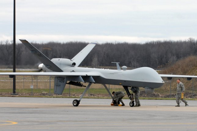 New York Air National Guard members rush to service an MQ-9 Reaper remotely piloted aircraft operated by the 174th Attack Wing taxies after it was launched and landed on a runway at Syracuse Hancock International Airport in Syracuse, N.Y. in 2015. Photo by Master Sgt. Raymond Drumsta/U.S. Army National Guard