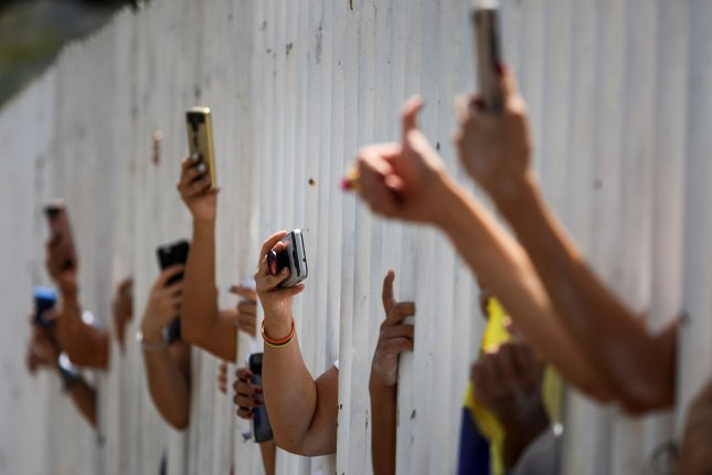 Aid volunteers take pictures with cellphones behind a fence as they attend a meeting with National Assembly President Juan Guaido in Caracas, Venezuela. Photo by Miguel Gutierrez/EPA-EFE