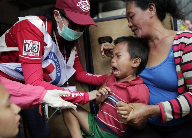 Philippine Red Cross health workers administer a measles vaccine to a boy during a nationwide response program to immunization people at a slum area in Manila, Philippines. Photo by Francis R. Malasig/EPA-EFE