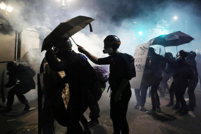 Activists at the Justice Center in Portland, Ore., clash with local and federal police on Monday. President Donald Trump sent federal police to multiple cities to protect government property from violent demonstrators. Photo by David Swanson/EPA-EFE