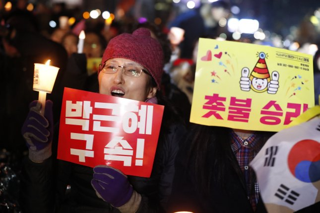 A South Korean woman holds a candle while gathering with others to celebrate after the court's ruling on the impeachment of South Korean President Park Geun-hye in Seoul, South Korea on Friday. A snap election is expected to take place in May. Photo by Jeon Heon-Kyun/EPA