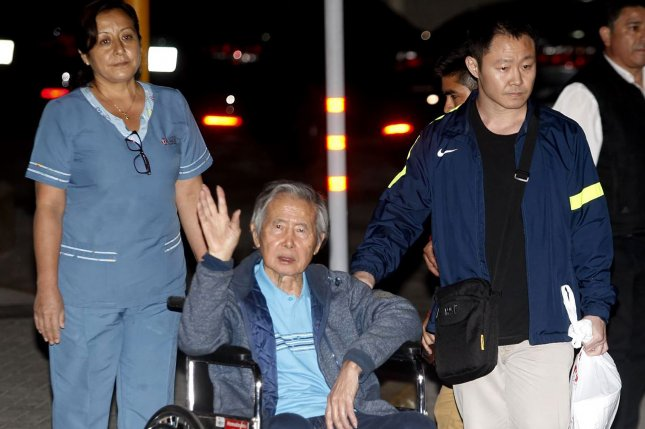 Former President Alberto Fujimori (C) is accompanied by his son, Kenji Fujimori, as he leaves the Centenario de Lima clinic, in which he was hospitalized for 12 days and after having been pardoned by the president, Pedro Pablo Kuczynski, in Lima, Peru, on Thursday. Photo by Eddy Ramos/EPA-EFE