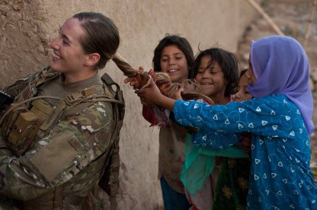 On Thursday, the Army said female soldiers may now wear a ponytail -- such as the one U.S. Army Sgt. Janean Sanders is pictured letting a group of Afghan girls play with -- that is as long as the bottom of their shoulder blades. File Photo by Sgt. Canaan Radcliffe/Defense Department