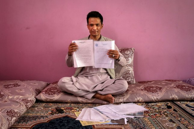 A former Afghan interpreter for U.S. forces, Abdul Rashid Shirzad, poses for a photograph as he is showing his documents during an interview at his house in Kabul, Afghanistan, earlier this month. File Photo by Hedayatullah Amid/EPA-EFE