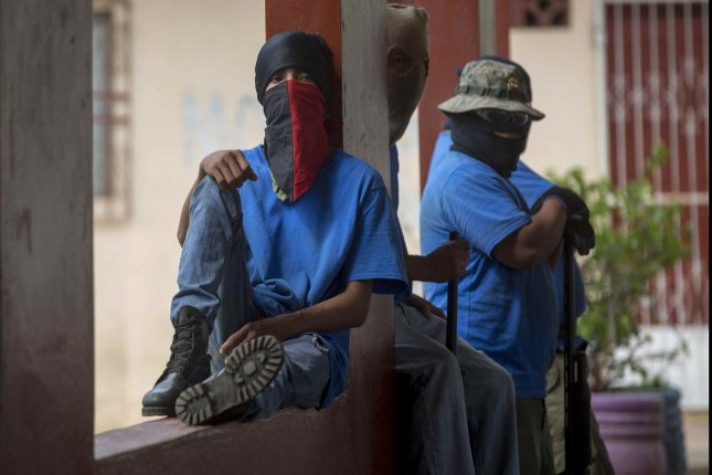Men with covered faces guard a square in Masaya, Nicaragua, on Wednesday, a day after the so-called Operation Cleaning. The government of Nicaragua took control of Masaya to remove road blocks and barricades. Photo by Jorge Torres/EPA-EFE