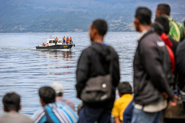 Residents wait at a port Wednesday as members of an Indonesian search and rescue team look for passengers from a sunken boat at Lake Toba, in North Sumatra, Indonesia. Photo by Dedi Sinuaji/EPA-EFE