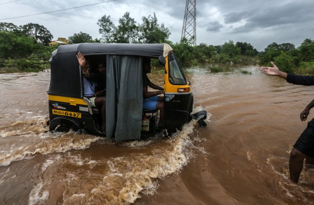 Indian people use an auto-rickshaw in the flooded street near the site of rescue operation carried out by National Disaster Response Force to rescue passengers stranded inside a train after it got stuck due to heavy rain near Vangani, on the outskirts of Mumbai, India, Saturday. Photo by Divyakant Solanki/EPA-EFE