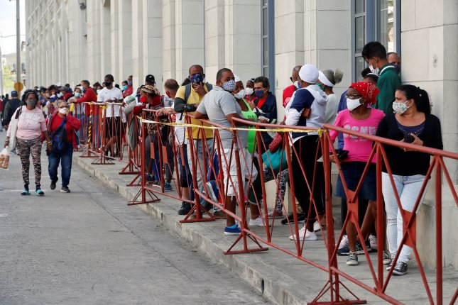 People wearing masks line up to buy food in a market in Havana, Cuba, on February 2. File Photo by Ernesto Mastrascusa/EPA-EFE