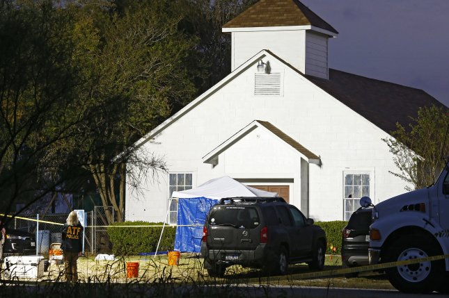 An ATF agent walks past cars and shot out windows of a church while investigators work at the scene of a mass shooting at the First Baptist Church in Sutherland Springs, Texas, on November 6, 2017. File Photo by Larry W. Smith/EPA-EFE