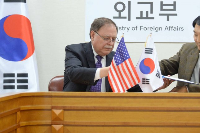 Timothy Betts (L), the U.S. negotiator for defense costs in South Korea, and his counterpart, Chang Won-sam, sign a provisional cost-sharing deal during their meeting at the Ministry of Foreign Affairs in Seoul on Sunday. Photo by Yonhap/EPA