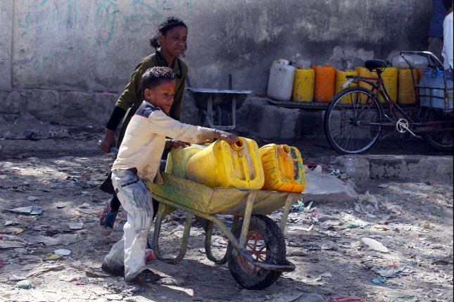 Yemeni children push a wheelbarrow with jerrycans filled with drinking water from a donated water pipe in Sanaa, Yemen, on November 18. File Photo by Yahya Arhab/EPA-EFE