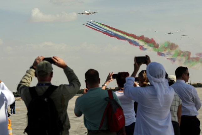 Visitors watch an Emirates Airbus A380 and the Al Fursan aerobatics demonstration team of the United Arab Emirates Air Force Sunday at the opening of the Dubai Airshow at Al Maktoum International Airport in Jebel Ali, Dubai, United Arab Emirates. Photo by Ali Haider/EPA-EFE