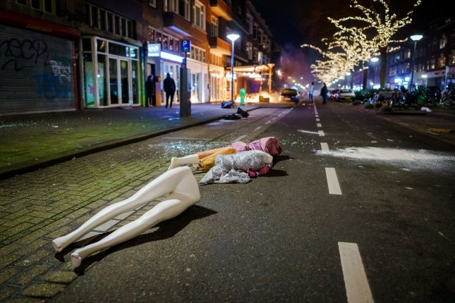 Parts of mannequins are seen strewn in a street on Monday night in Rotterdam, the Netherlands, during protests opposing coronavirus-related curfews and other restrictions. Photo by Marco de Swart/EPA-EFE