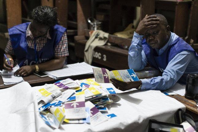 An election clerk reacts as he and others count votes at a polling station in Kinshasa, Democratic Republic of the Congo. The National Independent Electoral Commission postponed the release of provisional election results originally scheduled for Sunday. Photo by Stefan Kleinowitz/EPA