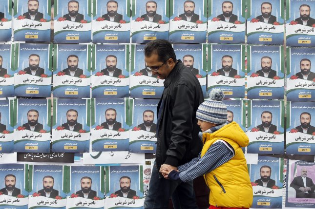 Iranians walk past electoral posters during the last day of election campaign on Wednesday in Tehran. Voters will go to the polls on Friday. Photo by Abedin Taherkenareh/EPA-EFE