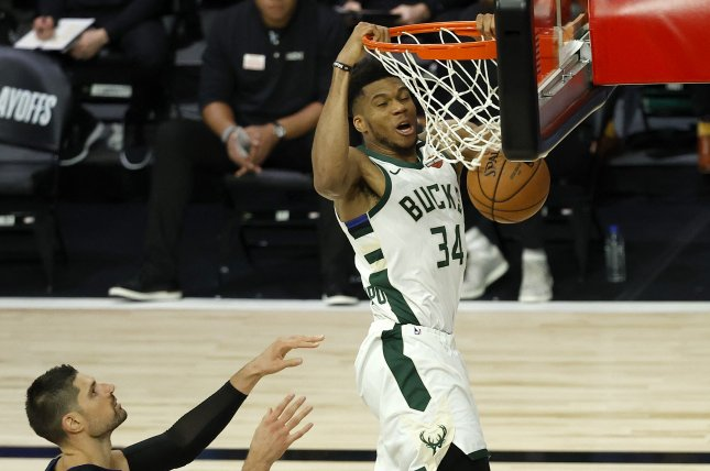Milwaukee Bucks forward Giannis Antetokounmpo (34) throws down a dunk as Orlando Magic center Nikola Vucevic (L) and Magic forward Wes Iwundu (R) look on during the second half in Game 4 on Monday at the ESPN Wide World of Sports Complex near Orlando, Fla. Photo by John G. Mabanglo/EPA-EFE