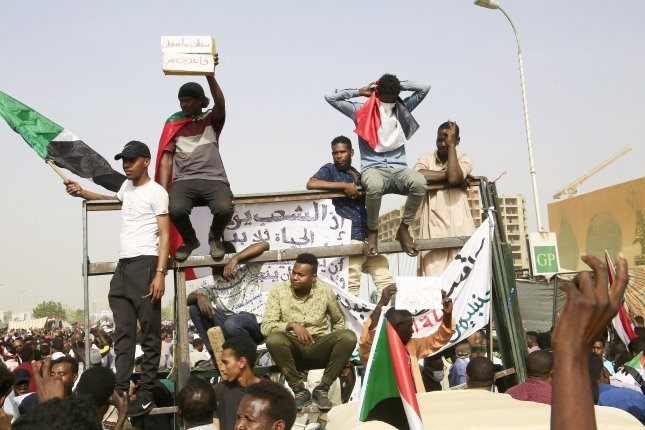 Demonstrators celebrate Thursday as they head towards the army headquarters amid rumors President Omar al-Bashir was removed from power. Photo by EPA-EFE