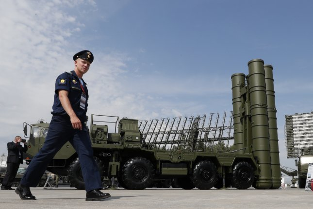A Russian military official walks in front of the S-400 Triumph anti-aircraft missile system. A report Monday said Russia has spent less on its military over the past two years. File Photo by Yuri Kochetkov/EPA-EFE