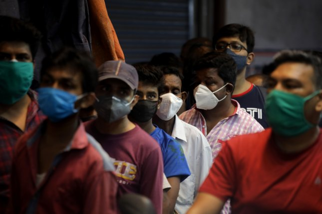Indian people wear protective face masks without maintaining social distancing outside a liquor shop Saturday after an announcement of a lockdown for the next 14 days in Kolkata, eastern India. Photo by Piyal Adhikary/EPA-EFE/PIYAL ADHIKAR