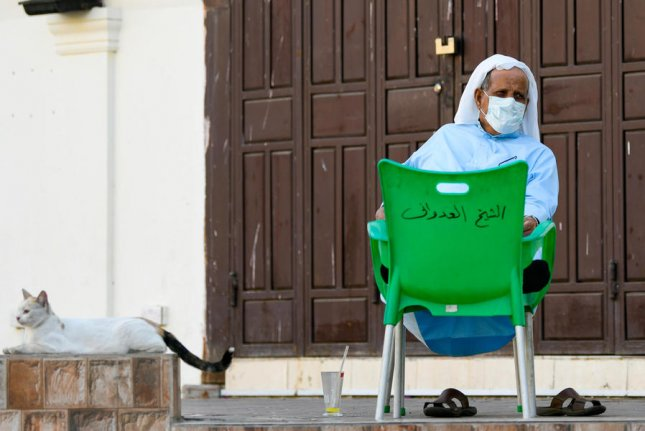 A man sits in front of a closed shop in Jeddah, Saudi Arabia, on March 24. The Saudi government said Tuesday it expects to lift all lockdown measures on June 21. File Photo by Ali Ahmad/EPA-EFE