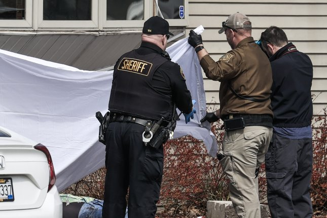 Law enforcement officers stood near the body of a victim Sunday as they investigated a mass shooting at a tavern in Kenosha, Wis., in which three people were killed. Photo by Tannen Maury/EPA-EFE