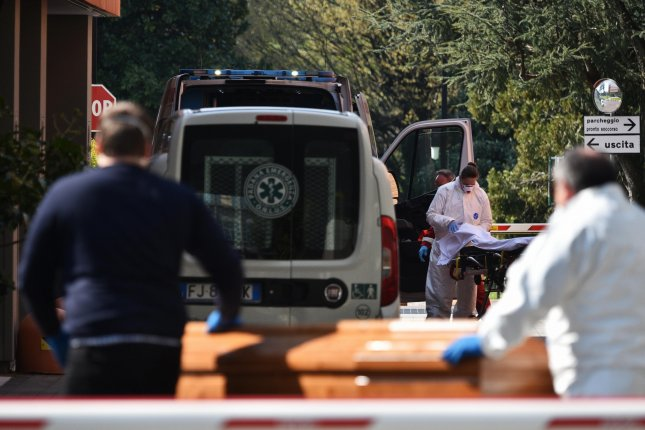 An ambulance arrives at Humanitas Gavazzeni hospital first aid service as workers of a funeral agency take away a body during the coronavirus crisis in Bergamo, Italy, on March 21. File Photo by Filippo Venezia/EPA-EFE