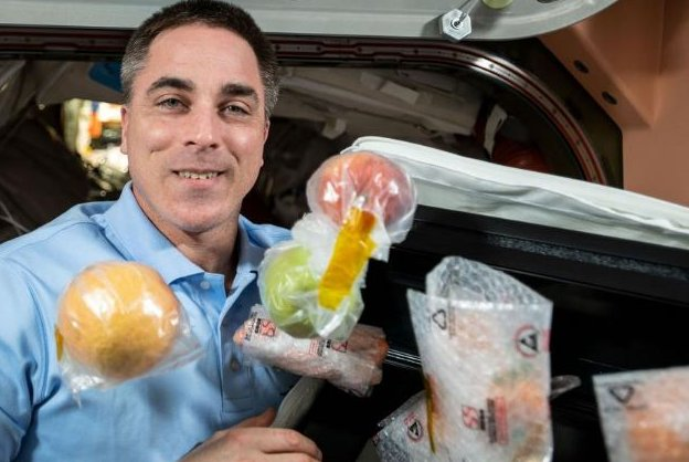Astronaut Chris Cassidy unpacks a box of food that was flown to the International Space Station in October as NASA planned a contest that seeks innovative ways to grow food in space. Photo courtesy of NASA