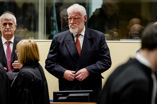 Slobodan Praljak enters the court in The Hague, Netherlands, Wednesday before committing suicide by drinking a chemical substance from a vial. Photo by Robin Van Lonkhuijsen/EPA