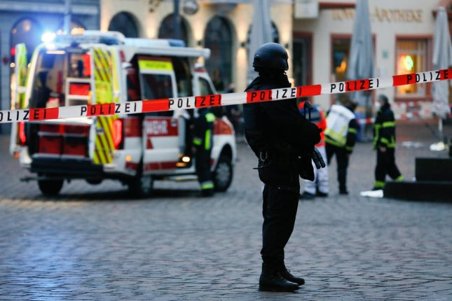 A police officer stands guard in the city center of Trier, Germany, on Tuesday after a man struck several pedestrians in the area. At least five died, authorities said. Photo by Julien Warnand/EPA-EFE