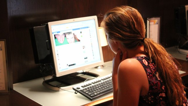A woman checks her Facebook in Washington, DC. Documents released by former NSA contractor Edward Snowden show programs used by the NSA have the capability to track virtually anything online. (UPI/Billie Jean Shaw)