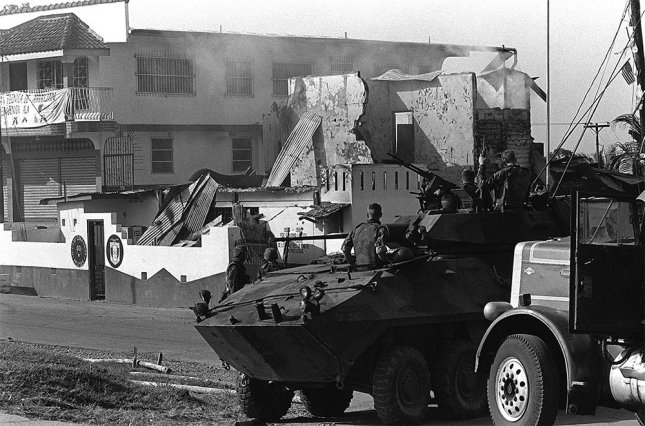 Marines of Company D, 2nd Light Armored Infantry Battalion, stand guard with their LAV-25 light armored vehicles outside a destroyed Panamanian Defense Force building during the first day of Operation Just Cause on December 20, 1989. Photo courtesy USMC