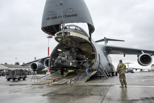 A U.S. Army AH-64 Apache helicopter is unloaded from an Air Mobility Command C-5M Galaxy at Ramstein Air Base in Germany on February 22. The four Apache helicopters that arrived are part of a larger contingent of helicopters and personnel participating in Operation Atlantic Resolve in support of NATO. File Photo by Staff Sgt. Timothy Moore/U.S. Air Force