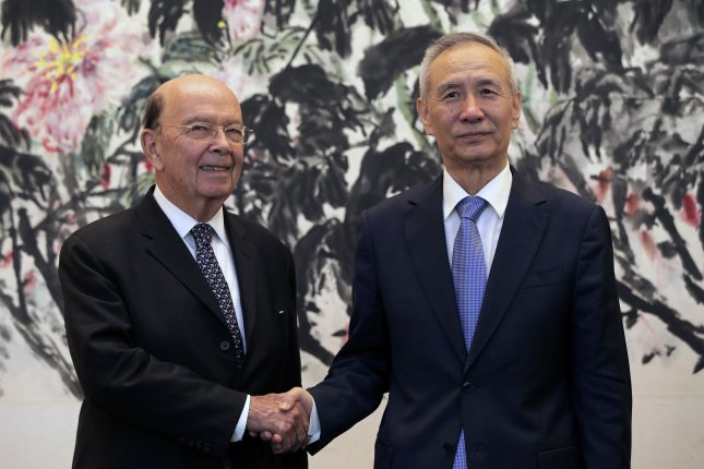 U.S. Commerce Secretary Wilbur Ross (L) shakes hands with Chinese Vice Premier Liu He as they pose for photographers after their meeting Sunday at the Diaoyutai State Guesthouse in Beijing, China. Photo by Andy Wong/pool/EPA