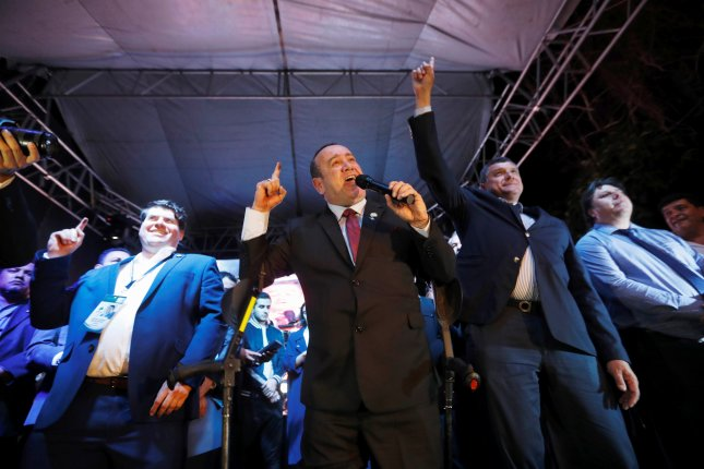 Alejandro Giammattei (C) of the Vamos party and the party's candidate for vice president Guillemo Castillo (2-R) celebrate victory during the preliminary election results at a press conference in Guatemala City, Guatemala, on Sunday. Photo by Esteban Biba/EPA-EFE