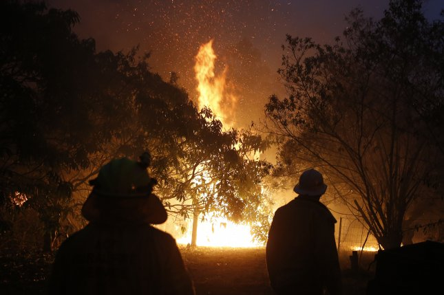Firefighters battle a blaze Tuesday north of Nabiac, New South Wales, Australia. Photo by Darren Pateman/EPA-EFE