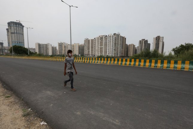 An Indian boy walks in a deserted road during the weekend lockdown in Noida, Uttar Pradesh, India, on Saturday. The Uttar Pradesh government imposed a lockdown and ordered extremely more testing after a review of the present situation of coronavirus. Photo by Harish Tyago/EPA-EFE