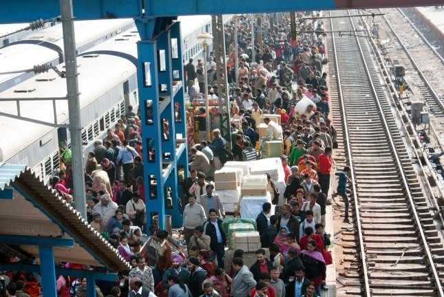 Train station platform filled with commuters in Delhi, India. Photo by Daniel Prudeck/Shutterstock
