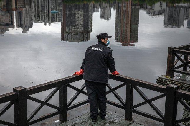 A public security person wearing a protective face mask stands in front of a lake in Wuhan, on Sunday. Photo by Roman Pilipey/EPA-EFE