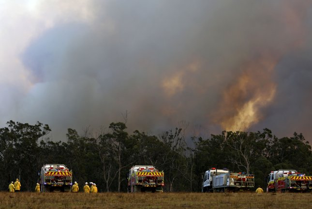Firefighters seek to contain a brush fire approaching in Old Bar, New South Wales, Australia, on Sunday. Photo by Darren Pateman/EPA-EFE