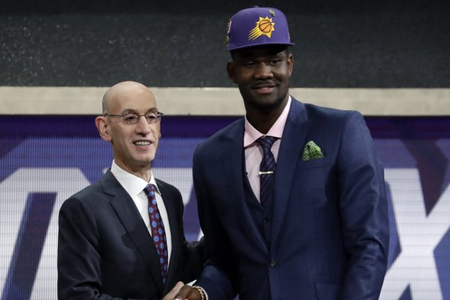 NBA commissioner Adam Silver (L) shakes hands with Deandre Ayton after being selected with the No. 1 overall pick by the Phoenix Suns in the first round of the 2018 NBA Draft on Thursday night at the Barclays Center in Brooklyn. Photo by Jason Szenes/EPA-EFE