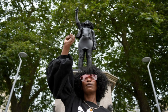 Protester Jen Reid with a raised fist poses in front of a depiction of herself, the statue A Surge of Power (Jen Reid) by British artist Marc Quinn, which was removed on Wednesday. Photo by Neil Hall/EPA-EFE