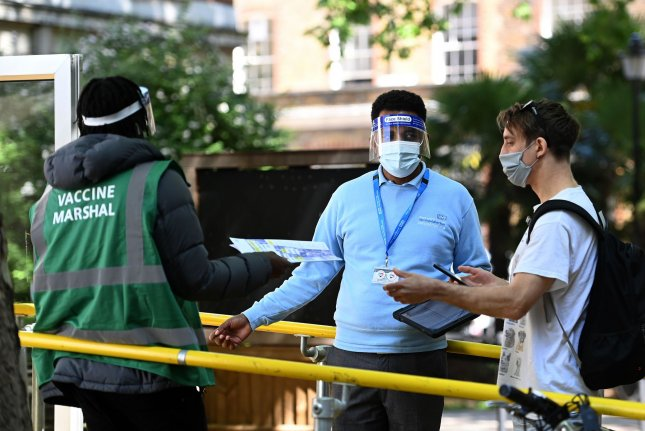 A young man enters a COVID-19 vaccination center in London earlier this week. Photo by Andy Rain/EPA-EFE