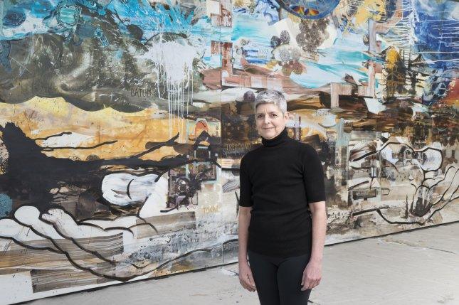 Chicago artist Jackie Kazarian stands before her painting, Armenia, which stands 11.5-by-26-feet tall. The painting was created to commemorate the 100th anniversary of the Armenian genocide. Photo by James Prinz
