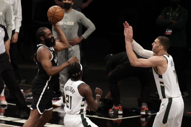 Brooklyn Nets guard James Harden (L) suffered the hamstring injury early in Game 1 against the Milwaukee Bucks on Saturday when he attempted to throw a lob pass over Milwaukee Bucks guard Jrue Holiday (21) and Bucks center Brook Lopez (R) in the first quarter. Photo by Jason Szenes/EPA-EFE
